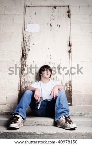 teen with handgun - teenager against wall holding gun