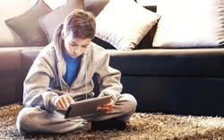 Teen with tablet sitting on the floor in the room