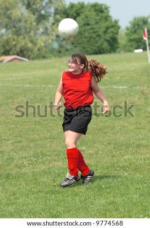 Teen Youth Girl Bouncing Soccer Ball off Head During Game.