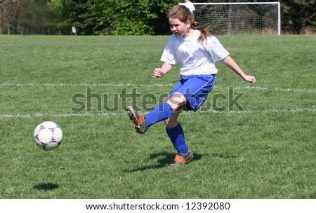 Teen Youth Girl kicking ball in air at soccer game.
