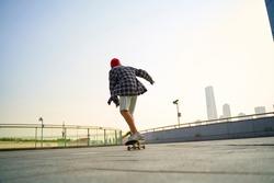 teenage asian child skateboarding outdoors on a pedestrian bridge
