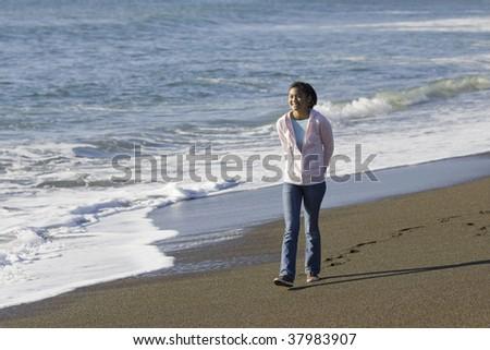 Teenage Asian Girl Walking along Waves at Beach
