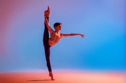 teenage ballet dancer dances barefoot under a colored light.