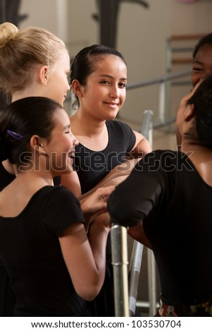 Teenage ballet dancer smiling with friends at class