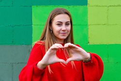 Teenage blonde girl with a red sweater. Making a gesture of heart. Green wall background