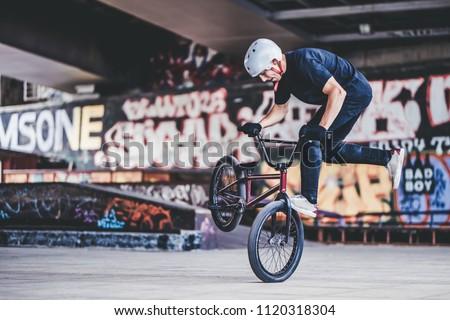 Teenage BMX rider is performing tricks in skatepark.