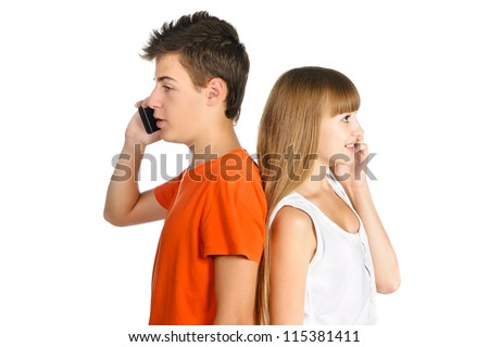 teenage boy and girl chatting on cell phones standing back to each other isolated over white