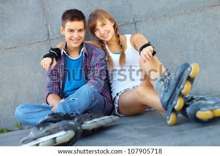 Teenage boy and girl having a rest after roller-skating