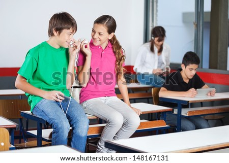 Teenage boy and girl looking at each other while listening music on mobilephone in classroom