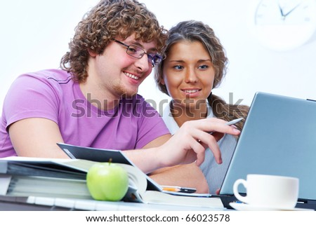 teenage boy and girl sitting in front of a laptop and do a fun learning