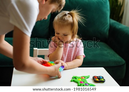 Teenage boy and his little sister playing  with trendy pop it fidget and simple dimple, sensory rainbow toys push pop, washable and reusable stress relief toys. A popular anti-stress toys for children