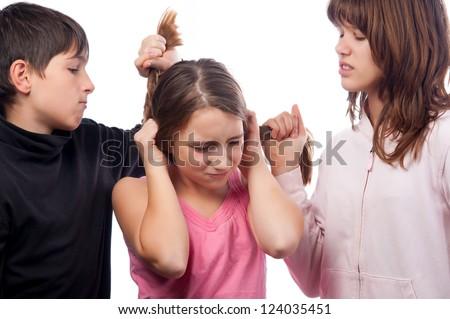 Teenage boy and teenage girl pulling hair of smaller teenage girl.