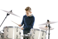 teenage boy behind drum kit in studio against white background