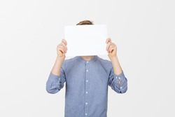 Teenage boy covering his face with a empty white paperT over white background. Teenage boy holding blank sheet of paper infront of his face. Baner concept.