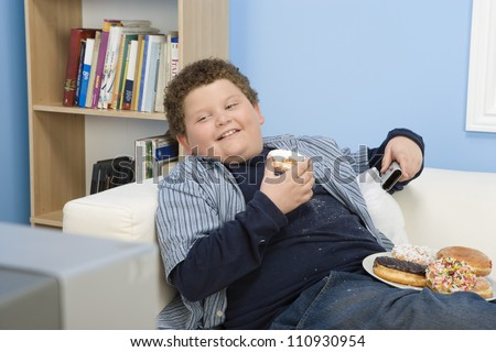 Teenage Boy Eating Donut And Watching Television