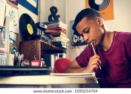 Teenage boy in a bedroom doing work thinking #1090254704