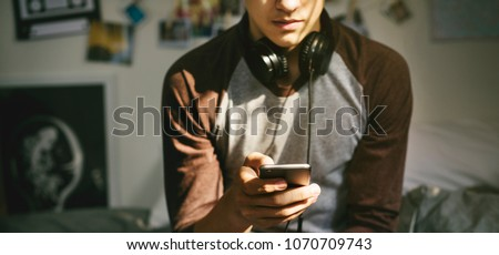 Teenage boy in a bedroom listening to music through his smartphone #1070709743