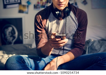 Teenage boy in a bedroom listening to music through his smartphone