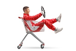 Teenage boy in a racing suit holding a steering wheel and sitting inside a shopping cart isolated on white background