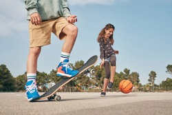 Teenage boy in activewear practicing in skateboarding near smiling girl exercising with basketball ball in sunny sports ground