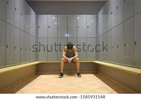 Teenage boy in gym locker room, looking down