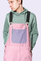 Teenage boy in pink dungarees and green hoodie streetwear photoshoot