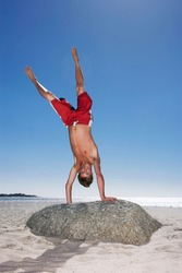Teenage boy (17-19) in red swimming shorts doing handstand on top of a rock at the beach