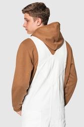 Teenage boy in white dungarees and brown hoodie streetwear photoshoot