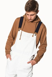 Teenage boy in white dungarees and brown hoodie streetwear photoshoot