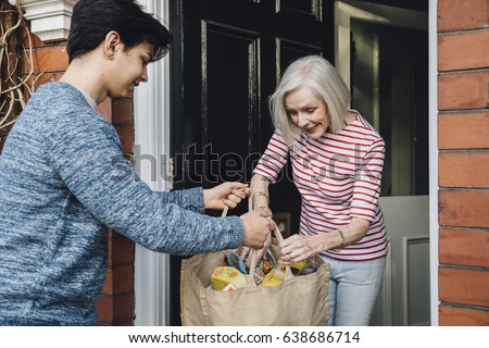 Teenage boy is delivering some groceries to an elderly woman. He is handing her a shopping bag at her front door.