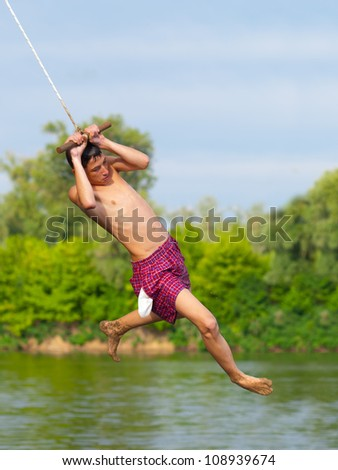 Teenage boy jumping into the river from swinging rope on sunny summer day.