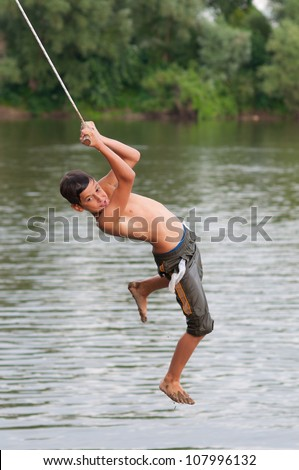 Teenage boy jumping into the river from the swinging rope.