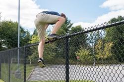 Teenage Boy jumping over a school yard fence, Canada.