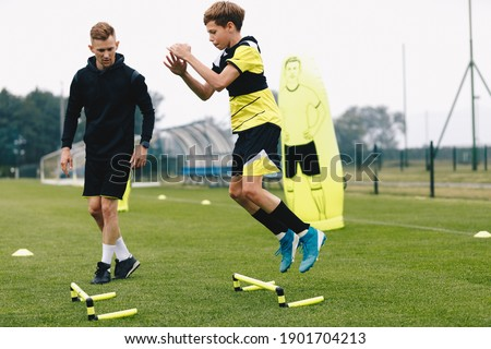 Teenage boy jumping over hurdles. Young soccer athlete practicing strength and agility skills. Boy of youth soccer team on training unit with personal trainer. Soccer coach coaches a young player