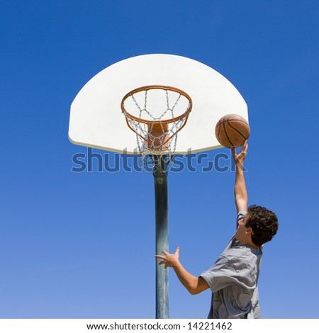 Teenage boy jumps to dunk a basketball