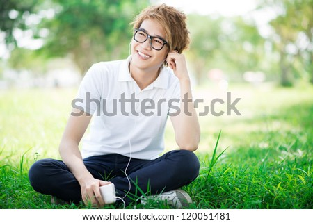 Teenage boy listening to mp3 outdoors