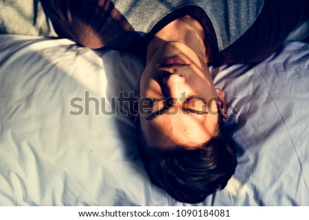Teenage boy lying down on bed sleepy nap and depression concept