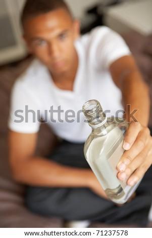Teenage Boy Lying  In Bedroom Drinking