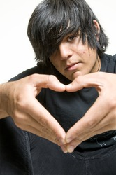 Teenage boy making heart symbol with hands