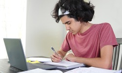 Teenage boy of Middle-Eastern ethnicity doing remote high school in times of Covid-19, sitting at table taking notes off a laptop.