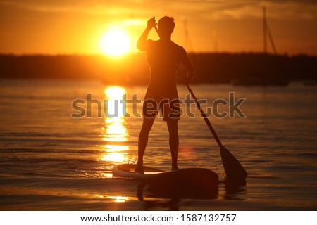 Teenage boy paddle boarding on lake at sunset, Lake Starnberg, Bavaria, Germany, Europe