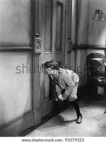 Teenage boy peeping through keyhole