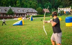 Teenage boy playing archery tag during summer