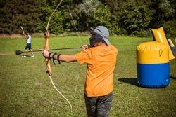 Teenage boy playing archery tag on a meadow