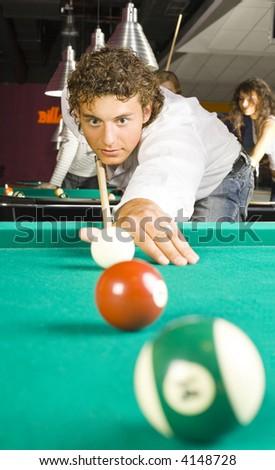 Teenage boy playing billard. In the background others teenagers also playing billard