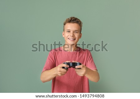 Teenage boy playing video game on color background #1493794808