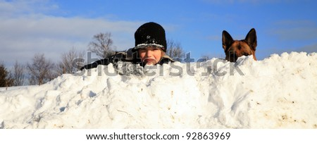 Teenage boy playing with dog in winter, sunny day on a meadow covered with snow.