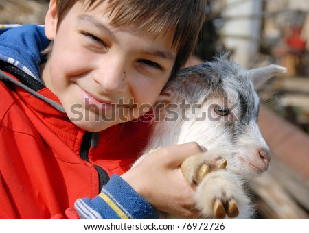 teenage boy portrait with young white goatling smiling outdoor