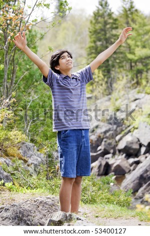 Teenage boy raising hands in praise to God outdoors on mountain