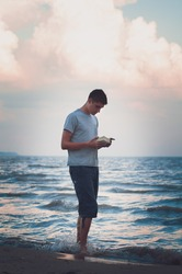 teenage boy reading a book while standing in the waters edge at a beach